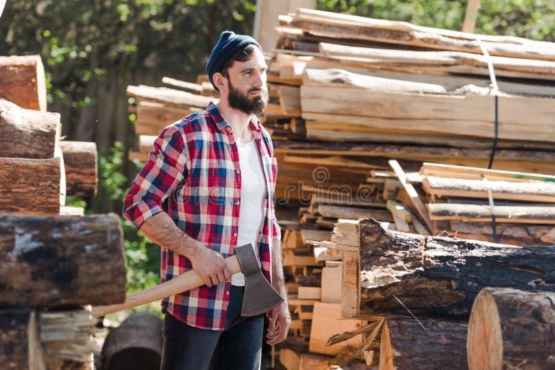 skäggig skogsarbetare i rutigt skjortaanseende med yxan royaltyfria foton