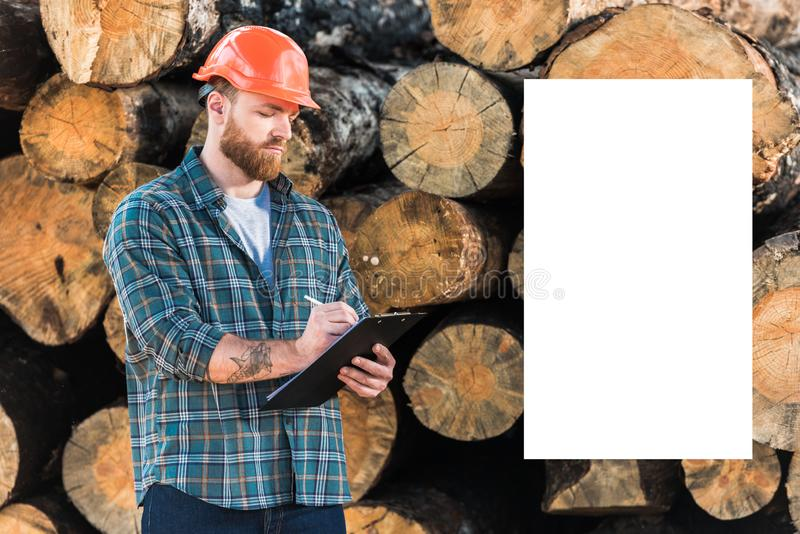 skäggig skogsarbetare i skyddande hjälmhandstil i skrivplatta och vitt tomt kopieringsutrymme på journaler royaltyfri fotografi