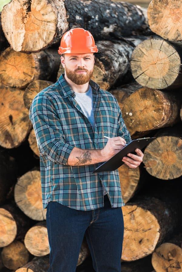 skäggig skogsarbetare i skyddande hjälmhandstil i skrivplatta på journaler fotografering för bildbyråer