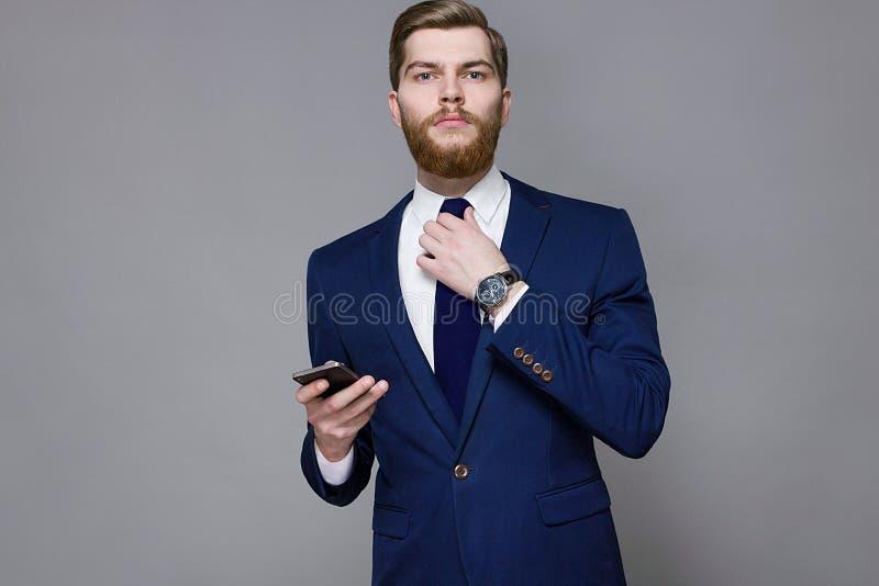 Skäggig stilig man som bär det smarta följet på en grå bakgrund arkivfoton