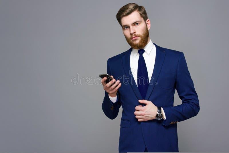 Skäggig stilig man som bär det smarta följet på en grå bakgrund royaltyfri bild