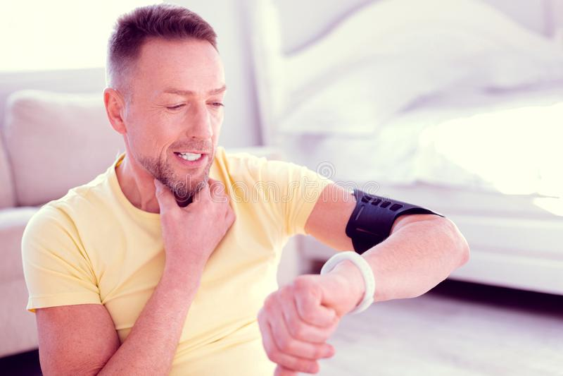 Skäggig stilig man som ser hans vita smarta klocka som kontrollerar dagaktivitet arkivfoto