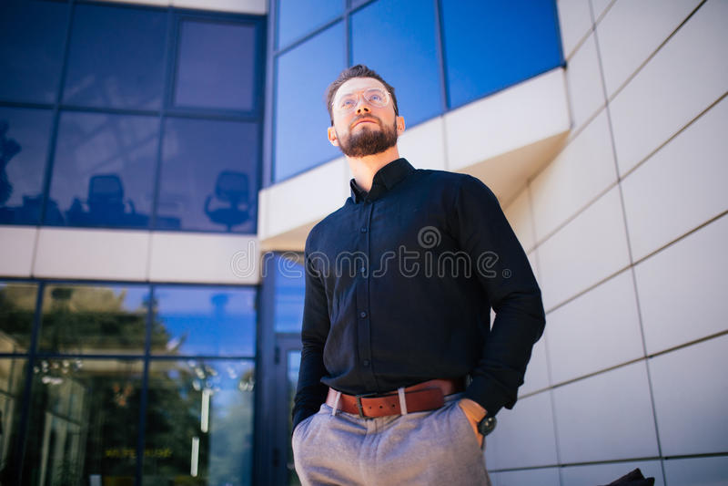 Skäggig stilig ung affärsman på kontorsbyggnad utomhus arkivbild