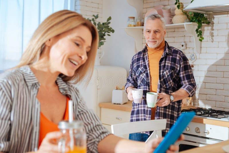 Skäggig svartögd affärsman som kommer med kopp te för hans fru arkivbild