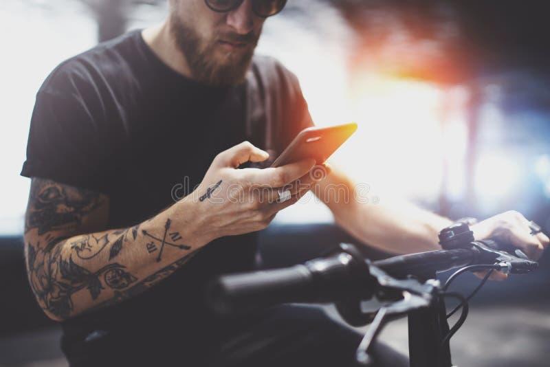 Skäggig tatuerad man i solglasögon genom att använda mobiltelefonen för för att överföra textmeddelandet, når att ha ridit med de royaltyfria foton