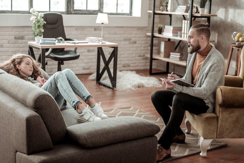 Skäggig terapeut som bär mörk byxa som lyssnar till hans klient arkivfoto