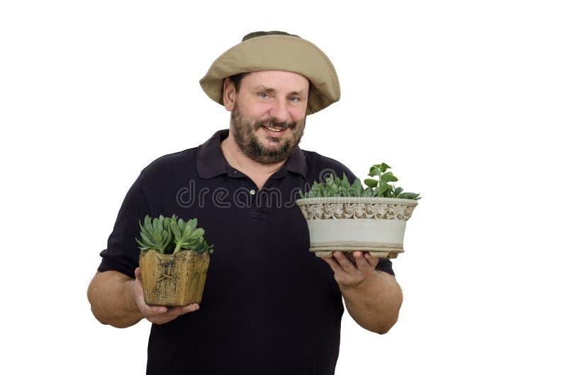 Skäggig trädgårdsmästare som rymmer två blomkrukor arkivfoton
