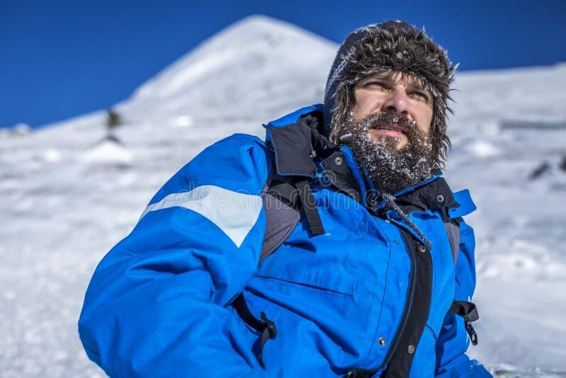 Skäggig trekker som vilar, medan klättra i vinter royaltyfri foto