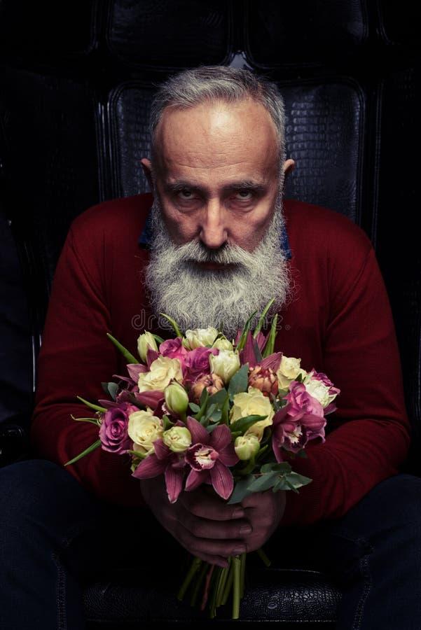 Skäggig tuff man som rymmer en bukett av tulpan och rosor royaltyfri foto