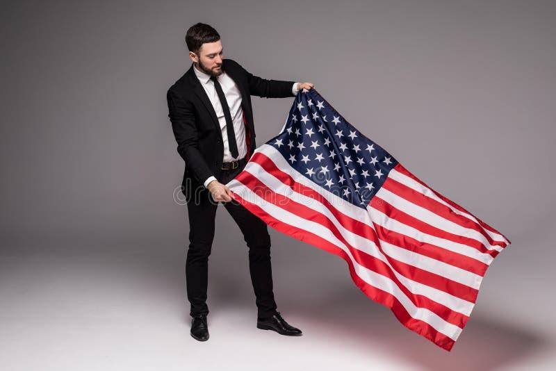 Skäggig ung affärsman i dräkten som rymmer USA flaggan och ser upp isolerad grå bakgrund royaltyfri fotografi