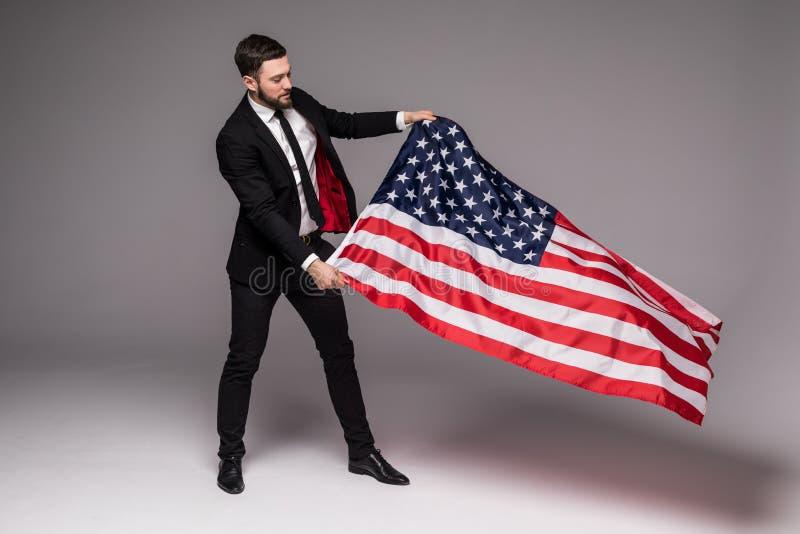 Skäggig ung affärsman i dräkten som rymmer USA flaggan och ser upp isolerad grå bakgrund arkivfoton