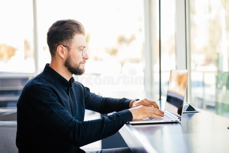 Skäggig ung affärsman i skjortasammanträde vid tabellen nära fönster med bärbara datorn i regeringsställning fotografering för bildbyråer
