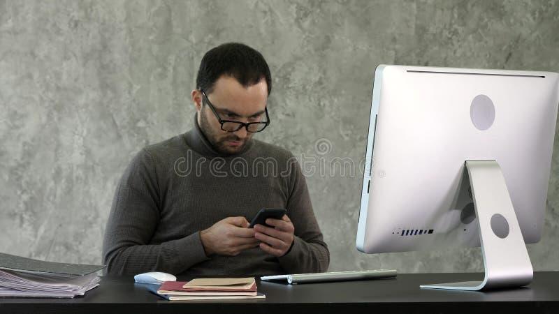 Skäggig ung affärsman som arbetar på det moderna kontoret Man som ser i hans smartphone och skriver något fotografering för bildbyråer