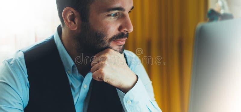 Skäggig ung affärsman som arbetar på modernt kontor på natten Tänkande se för konsulentman i bildskärmdator Chefmaskinskrivningno arkivfoto