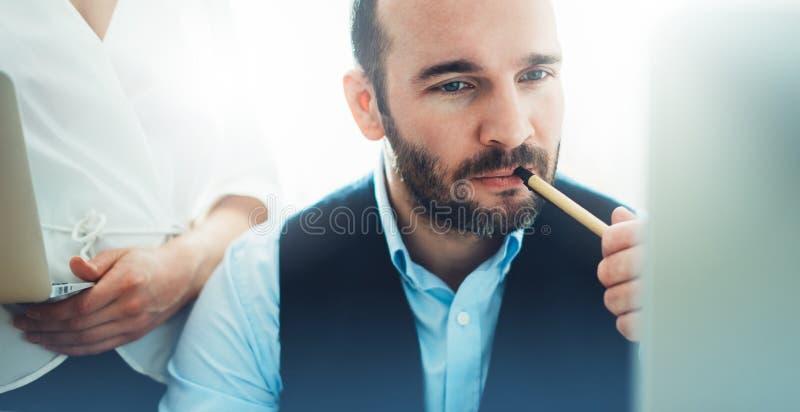 Skäggig ung affärsman som arbetar på modernt kontor Tänkande se för konsulentman i bildskärmdator Chef som coworking på arbete royaltyfri fotografi