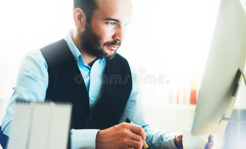 Skäggig ung affärsman som arbetar på modernt kontor Tänkande se för konsulentman i bildskärmdator Chefmaskinskrivning fotografering för bildbyråer