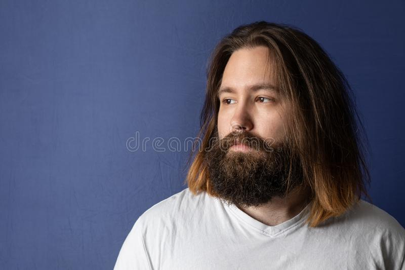 Skäggig ung man med långt hår royaltyfria bilder