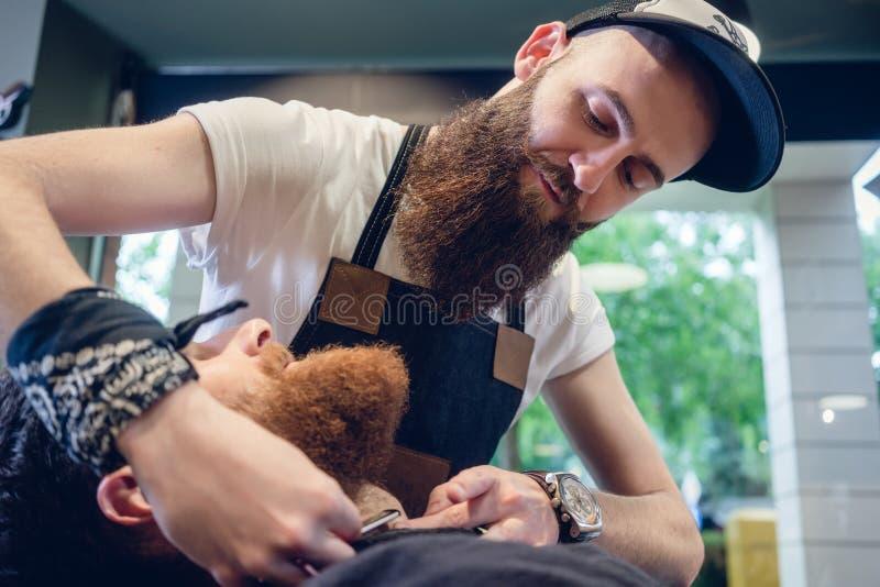 Skäggig ung man som är klar för att raka i hårsalongen av en expertis royaltyfri fotografi