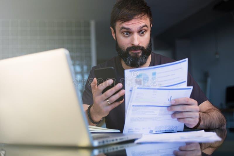 Skäggig ung man som arbetar med hemmastadda bläddra dokument för bärbar dator Affärsman som går till och med hemmastatt kontor fö royaltyfri bild