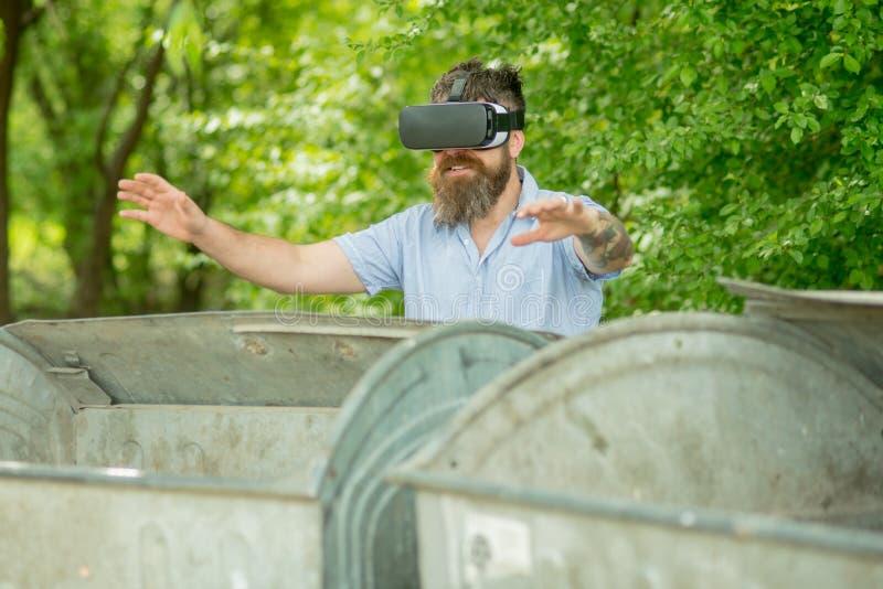 Skäggiga exponeringsglas för mankläder VR på avfalldumpsters Mannen med skägget undersöker miljön med grejen Hipster med mobilen arkivfoton