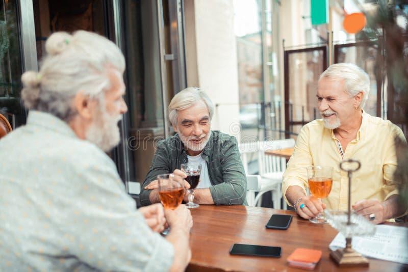 Skäggiga grå färg-haired män som dricker alkohol och samtal royaltyfria foton