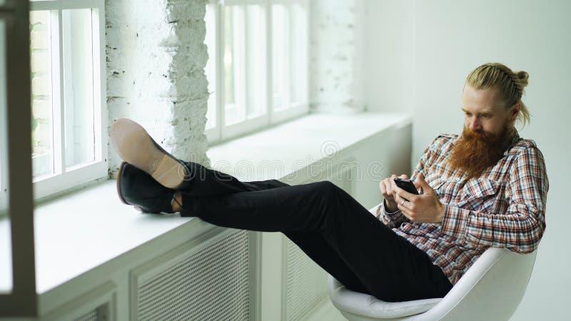 Skäggiga unga hipstermansms som smsar genom att använda smartphonen, medan sitta i offcestol med hans ben på fönsterbräda royaltyfri fotografi