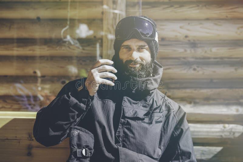 Skäggigt le snowboarded ta vilar efter rittperiod Ung man som dricker koppen av varmt te på solig terrass _ royaltyfria bilder