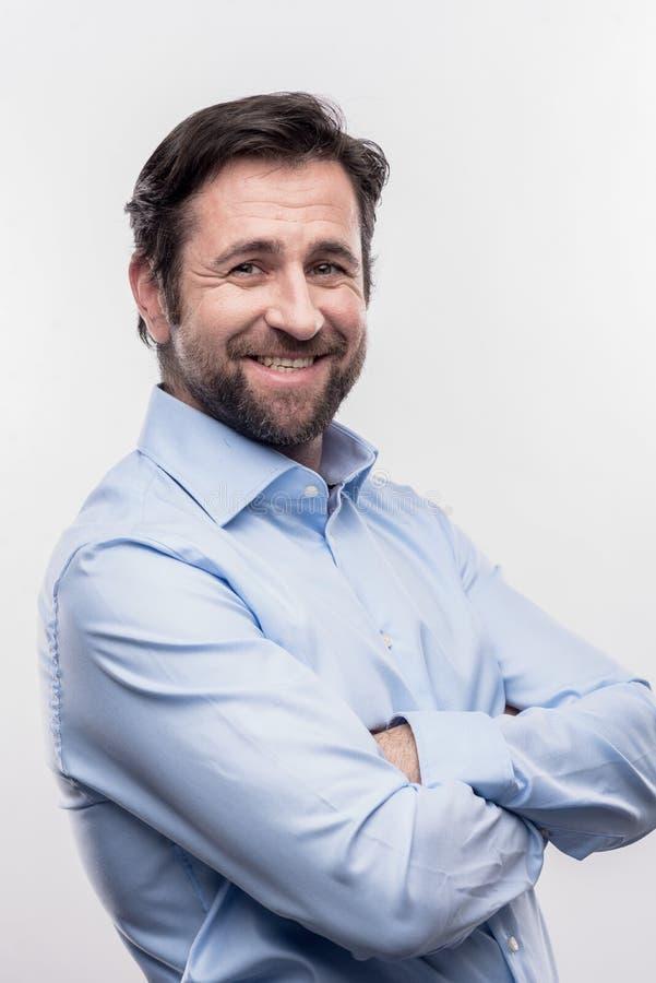 Skäggigt mörker-haired anseende för kontorschef på framdel av den vita väggen royaltyfri fotografi