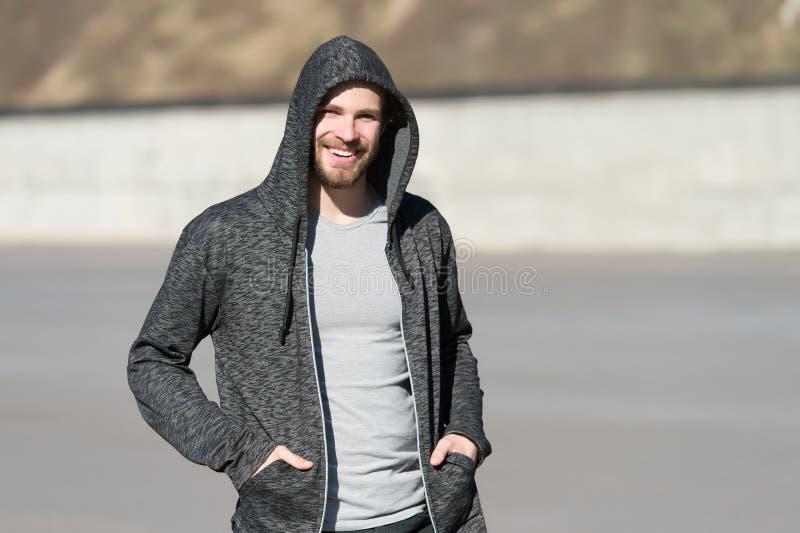 Skäggigt manleende i huven på soligt utomhus-, mode Macho lyckligt le i tröja, tillfällig stil Mäns mode, stil, sportsw arkivbilder