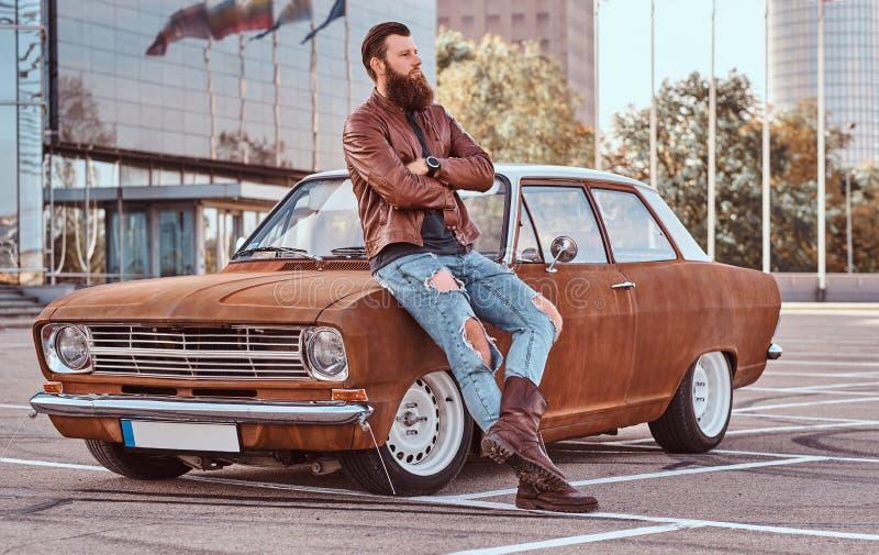 Skäggigt manligt iklätt bruntläderomslag och kängor som lutar på den stämda retro bilen i staden som parkerar nära skyskrapa fotografering för bildbyråer