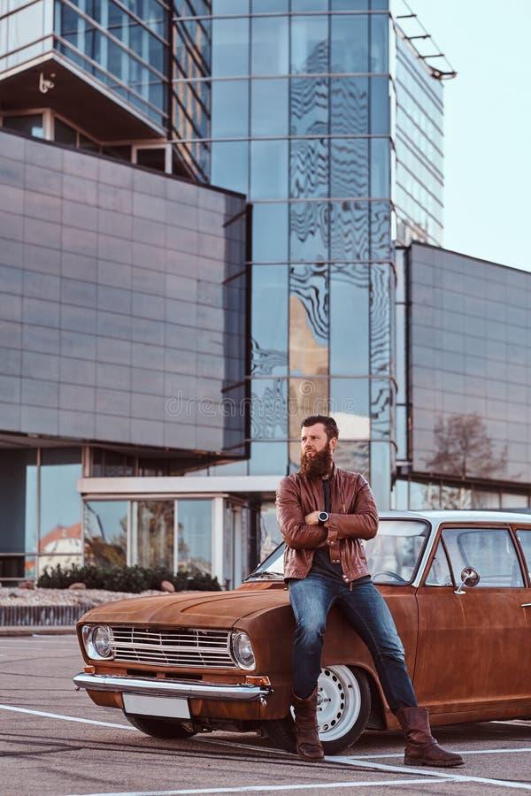 Skäggigt manligt iklätt bruntläderomslag och kängor som lutar på den stämda retro bilen i staden som parkerar nära skyskrapa royaltyfri fotografi