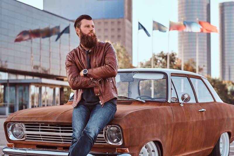Skäggigt manligt iklätt bruntläderomslag och kängor som lutar på den stämda retro bilen i staden som parkerar nära skyskrapa royaltyfri bild