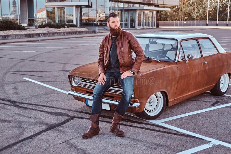 Skäggigt manligt iklätt bruntläderomslag och kängor som lutar på den stämda retro bilen i staden som parkerar nära skyskrapa arkivfoton