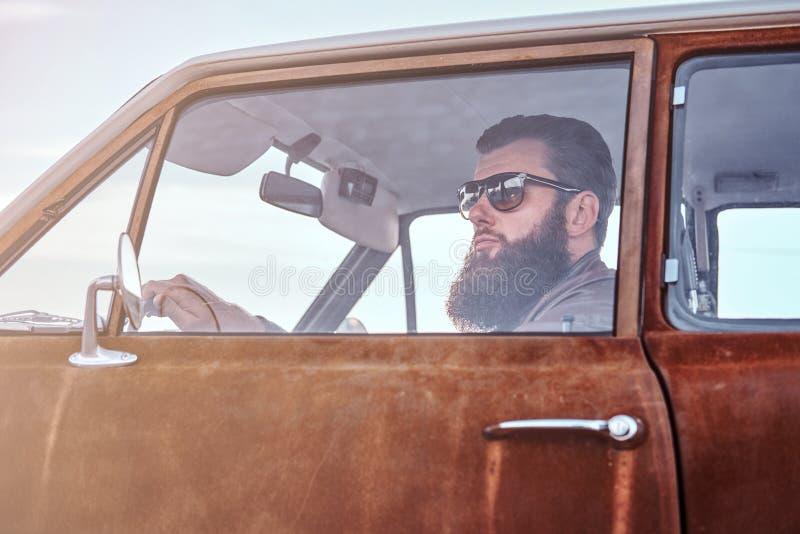 Skäggigt manligt iklätt bruntläderomslag som kör en retro bil arkivfoto