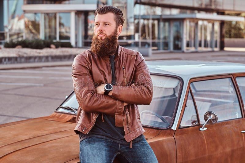 Skäggigt manligt iklätt bruntläderomslag som lutar på den stämda retro bilen i stadsparkeringen royaltyfria bilder