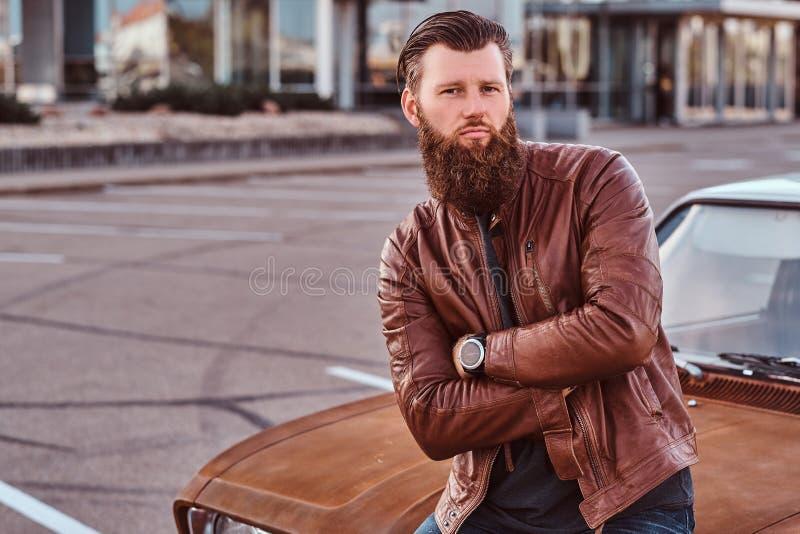 Skäggigt manligt iklätt bruntläderomslag som poserar med korsade armar, medan luta på den stämda retro bilen i staden fotografering för bildbyråer
