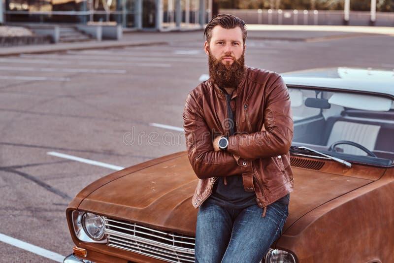 Skäggigt manligt iklätt bruntläderomslag som poserar med korsade armar, medan luta på den stämda retro bilen i staden arkivbilder