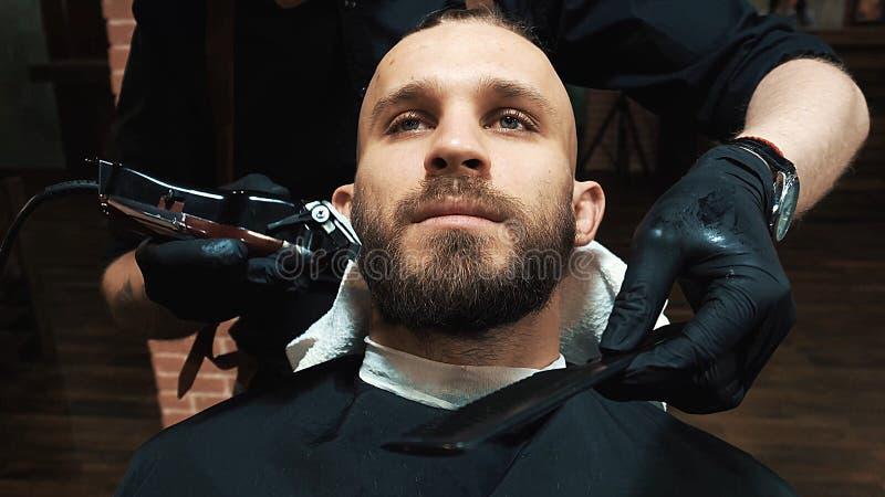 Skäggigt mansammanträde för barn i frisersalong royaltyfri foto