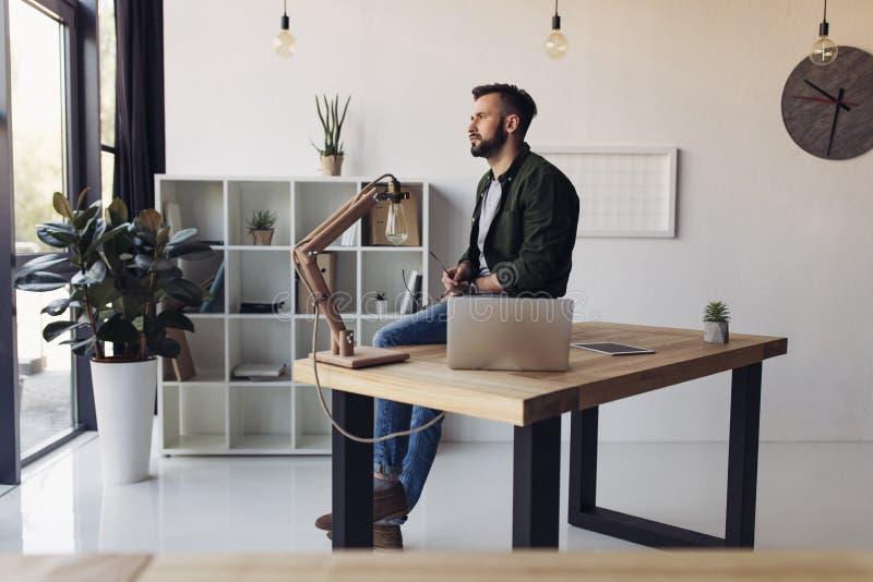 Skäggigt mansammanträde på tabellen med bärbara datorn och se fönstret fotografering för bildbyråer