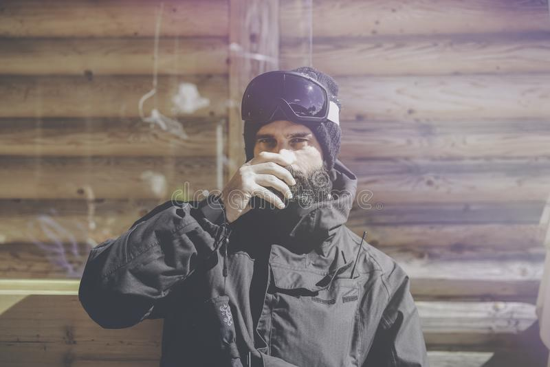 Skäggigt stiligt snowboarded ta vilar efter rittperiod Ung man som dricker koppen av varmt te på solig terrass _ arkivbilder