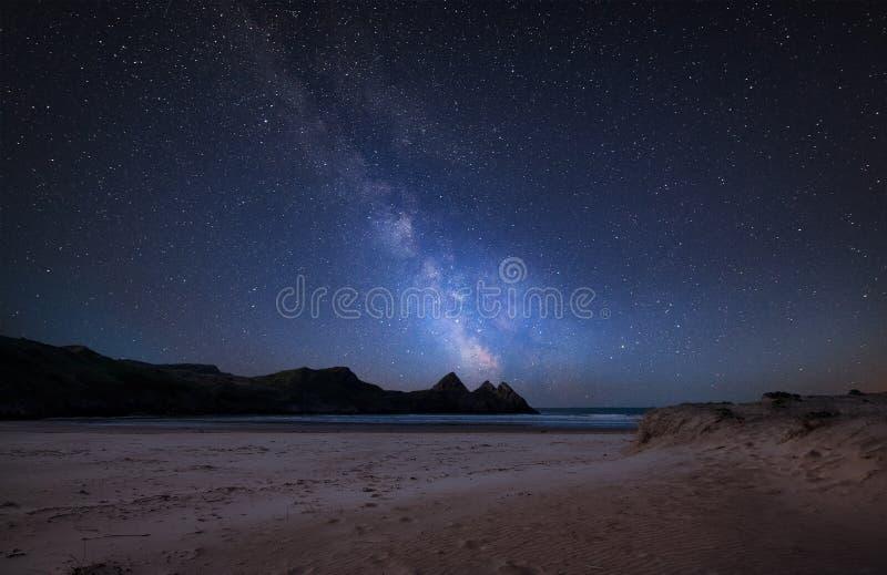Skäller den sammansatta bilden för den vibrerande Vintergatan över landskap av gula klippor för sandig strand tre arkivbild