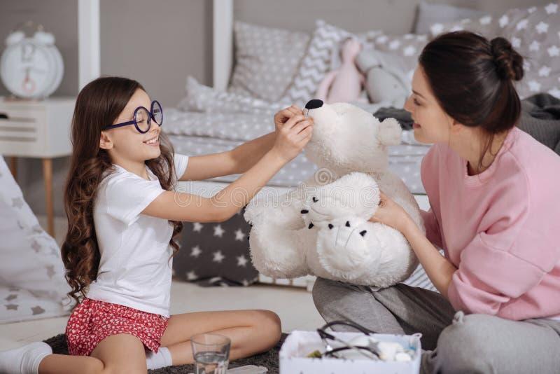 Skämtsam dotter och moder som har gyckel hemma royaltyfri foto