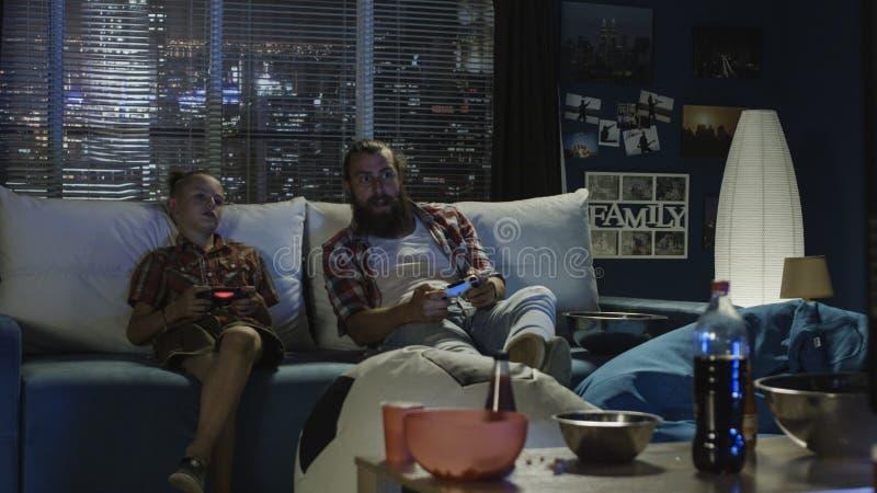 Skämtsam fader och son som har roligt och spelar videogamen royaltyfri foto