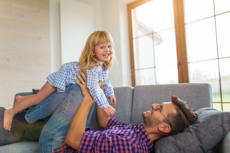 Skämtsam fader som uppe i luften balanserar dottern på ben på soffan arkivbild