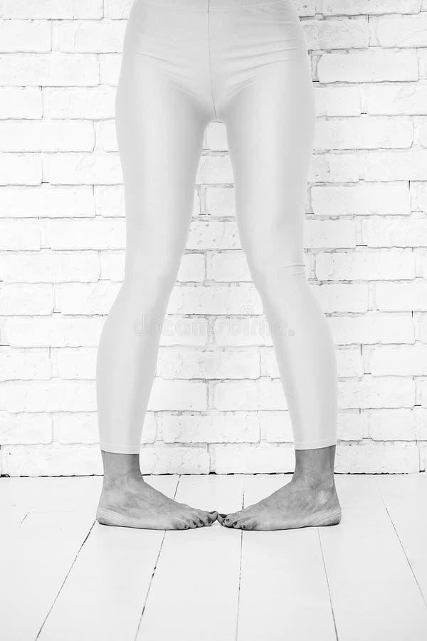 Skämtsam flicka i galen dansbalettposition av fot kvinna i orange damasker på ben Dans till rytm av din hjärta arkivbild
