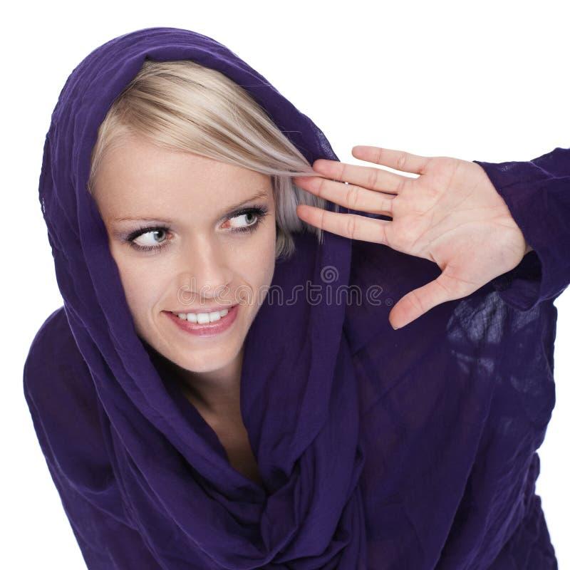Skämtsam kvinna i en med huva överkant som från sidan plirar royaltyfri fotografi