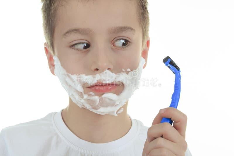 Skämtsam liten ung pojke som rakar framsidan över vit arkivbild