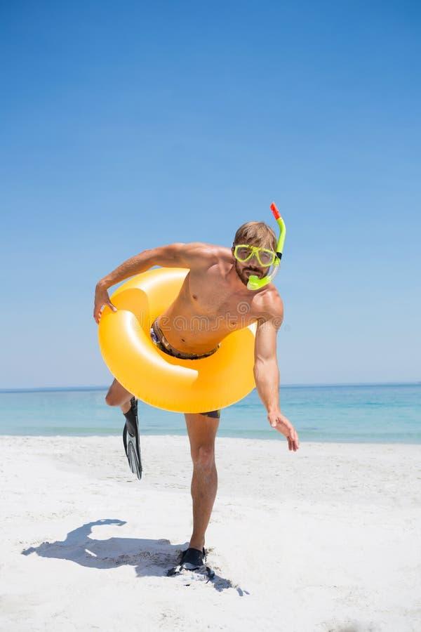 Skämtsam man med snorkeln som bär den uppblåsbara cirkeln arkivfoto