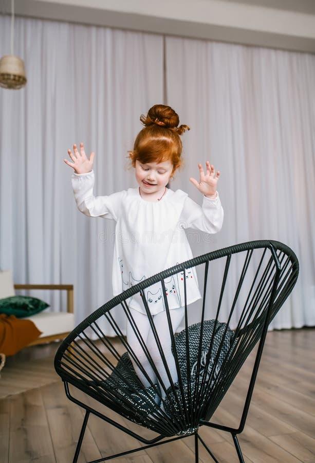 Skämtsam rödhårig manliten flickadans på stol hemma fotografering för bildbyråer