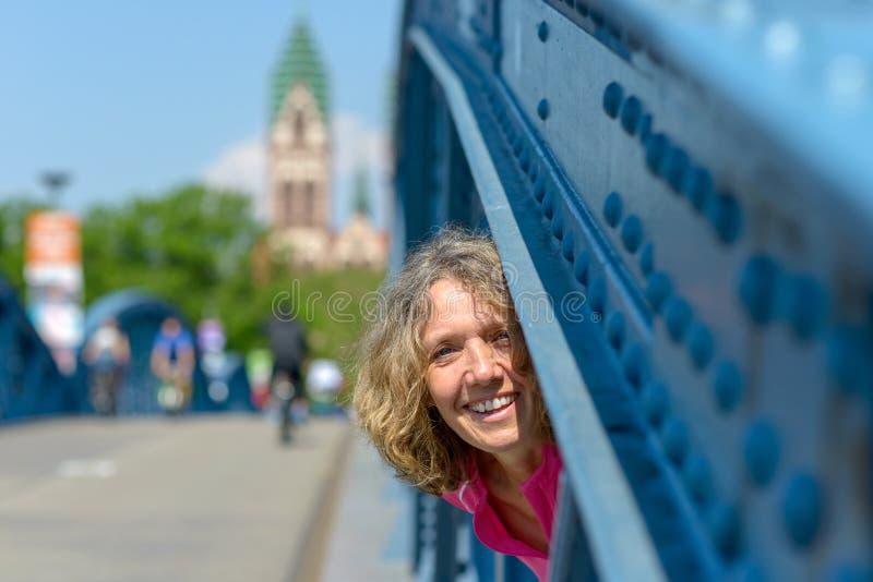 Skämtsam skratta kvinna som plirar till och med en bro royaltyfri fotografi